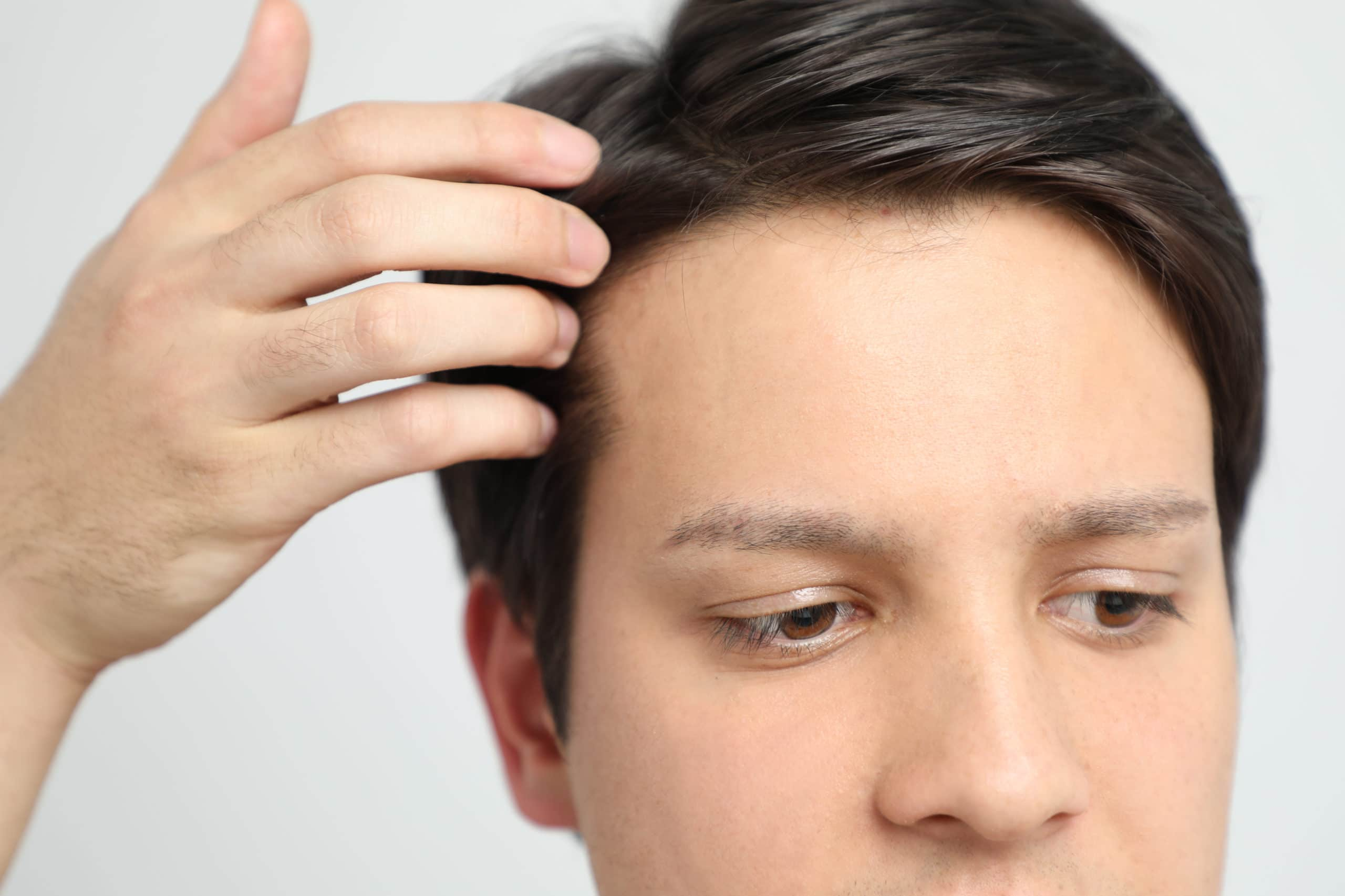 Man touching full head of hair